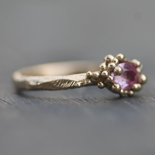 Oval pink sapphire surrounded by golden bubbles in 14k yellow gold