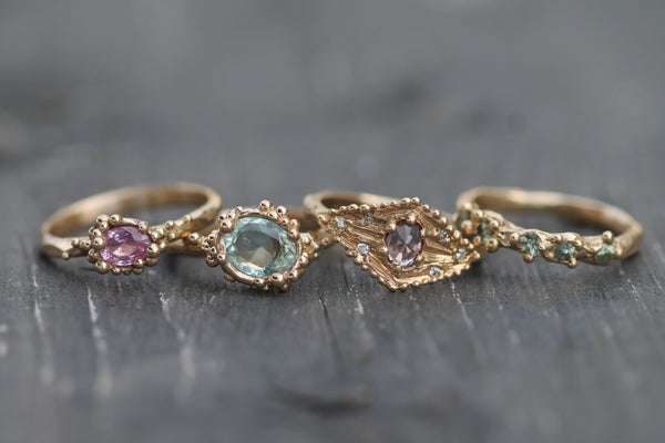 Mermaid treasure collection of rings beside one another.  Featuring sapphires, diamonds and aquamarine set in 14k yellow gold.