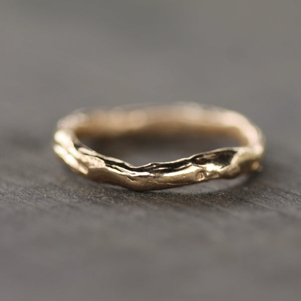 Hand carved gold wedding with texture reminiscent to flowing water