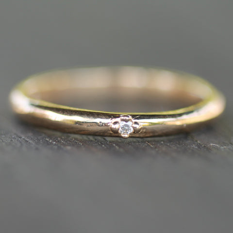 Simple, smooth and soft band with a slightly irregular organic quality.  This ring is made in 14 yellow gold with a 1.5mm diamond.