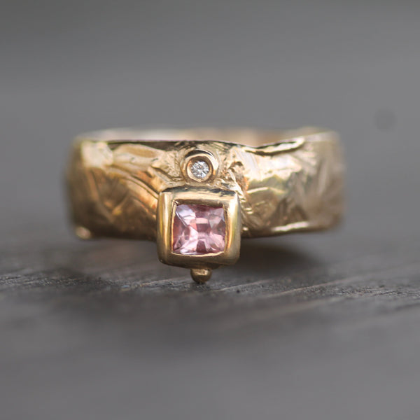 Hand carved textured gold ring with a 7mm wide band.  This ring has a pink sapphire and an adjacent small diamond.