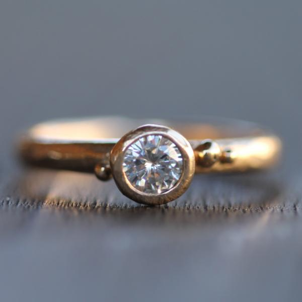 This ring balances classic solitaire design, with contemporary, playful charm. It has a subtly hand carved texture that is reminiscent of a naturally smoothed beach pebble. There are three little gold droplets around the center diamond to add natural sparkle.