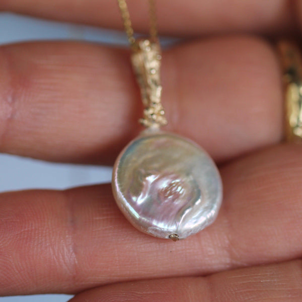 Mother moon pendant pictured on a hand to show the scale