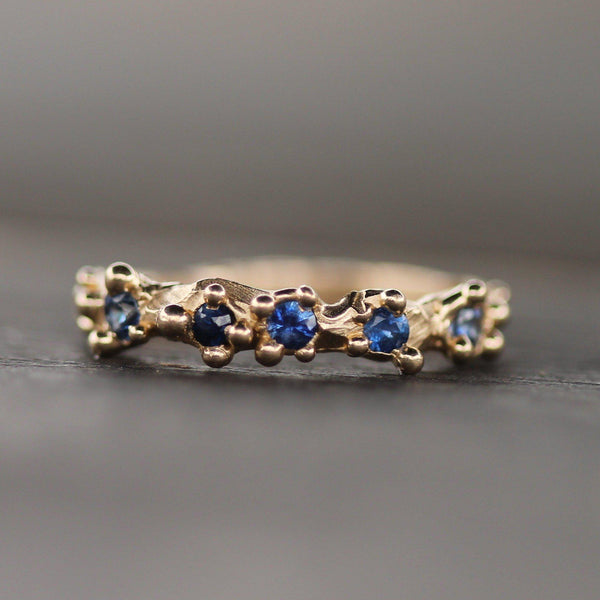 Mermaid Treasure ring with different hues of blue sapphires surrounded by bubbles