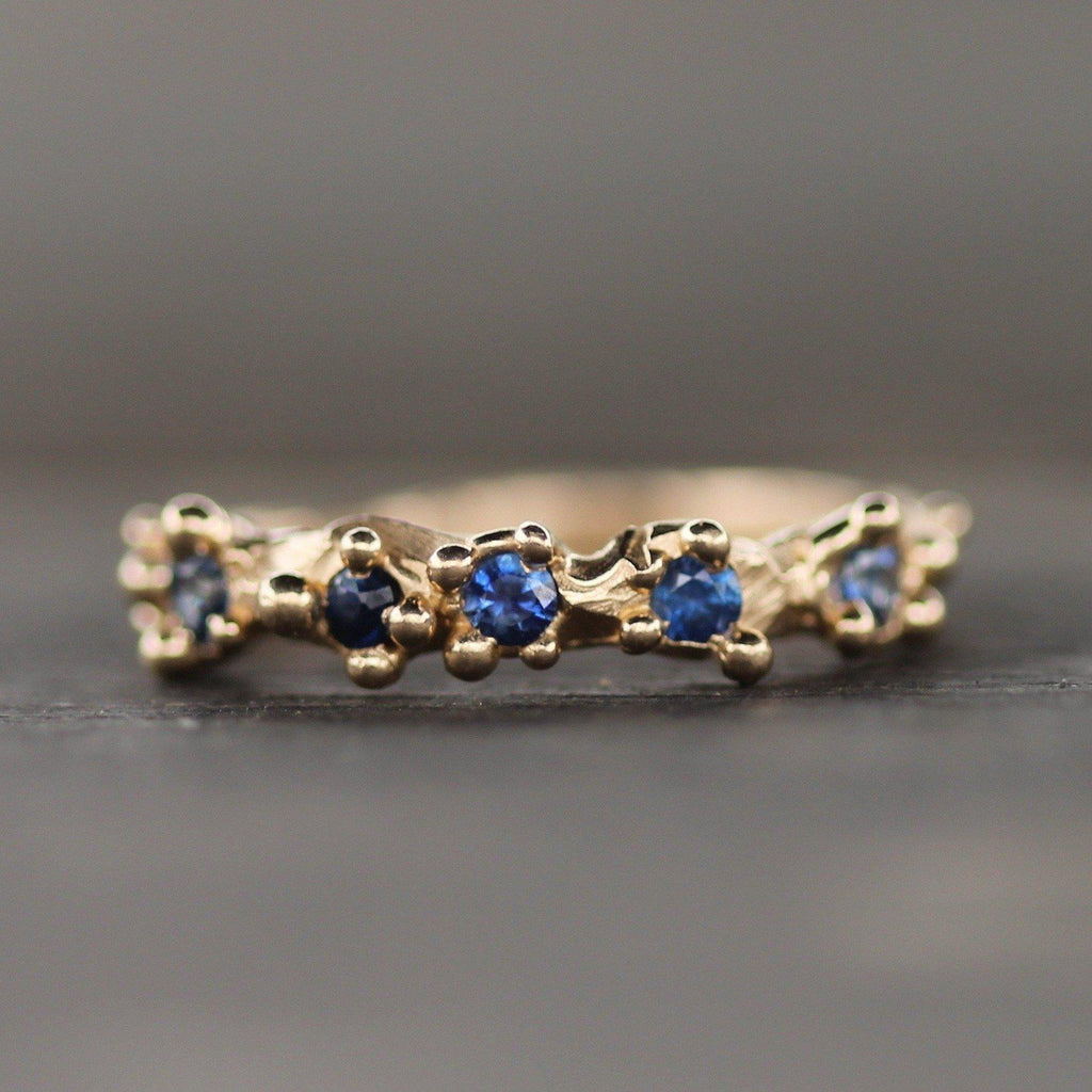 14k yellow gold ring with 5 blue sapphires surrounded by bubbles