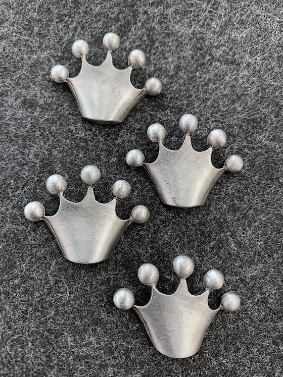 Four pewter magnets in the shape of crowns that come to five points that are topped with circles at the top.
