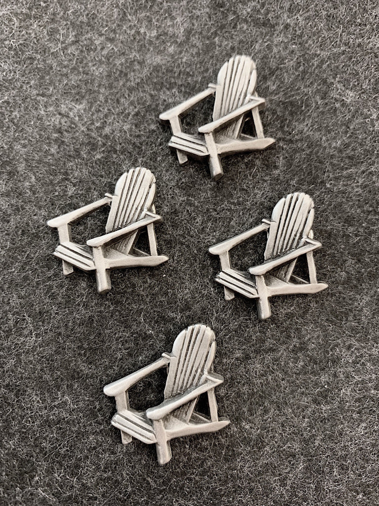 Four pewter magnets in the shape of muskoka lounge chairs.