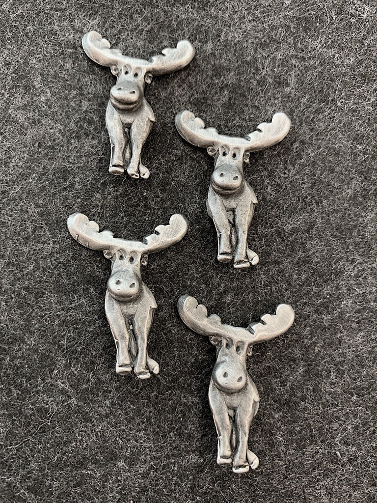 Four pewter magnets in the shape of smiling moose.
