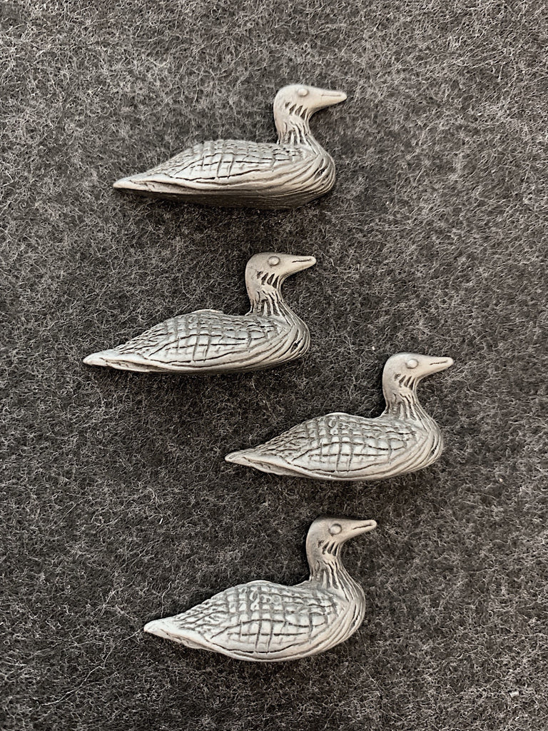 Four pewter magnets in the shape of loons, with lines showing feathers and wings.