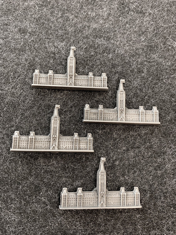 Four pewter magnets in the shape of the Canadian Parliament building with a flag raised on top of the Peace Tower.
