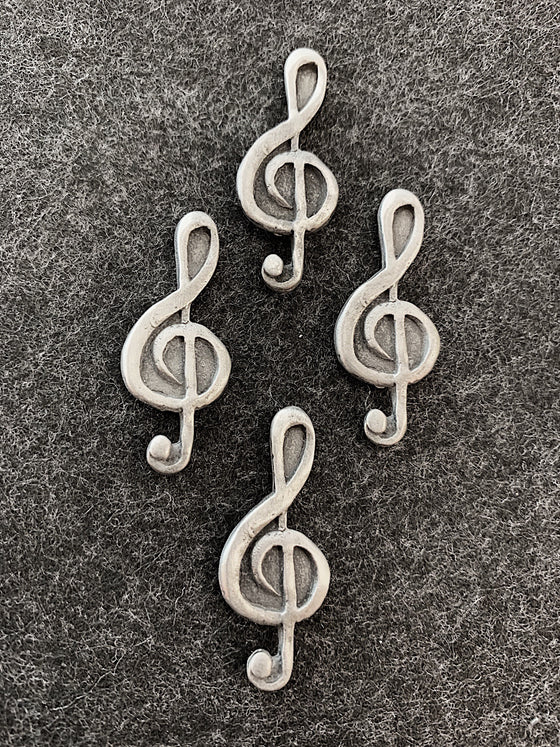 Four pewter magnets in the shape of treble clefs.