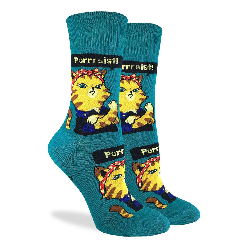 "These fun socks feature an image of Rosie the Riveter as a tabby cat with the phrase ""Purrsist"" above. This image is on a background of teal. Spandex added to the 85% cotton blend gives the socks the perfect amount of stretch to hug your feet."