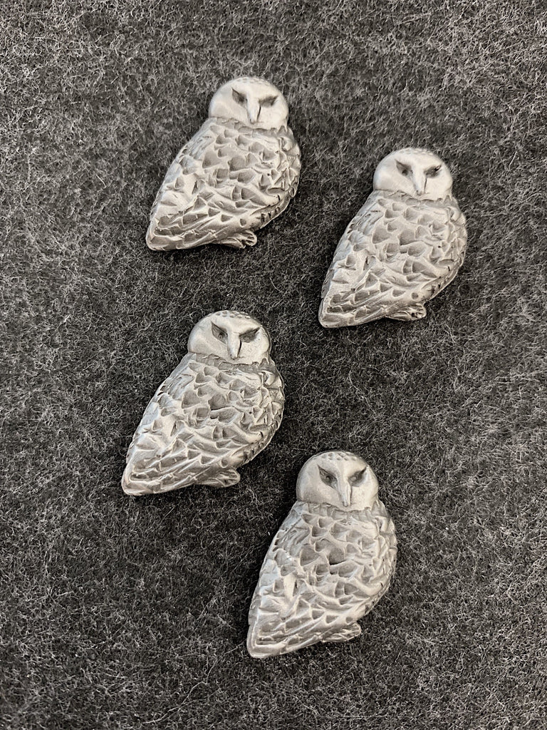 Four pewter magnets in the shape of snowy owls.