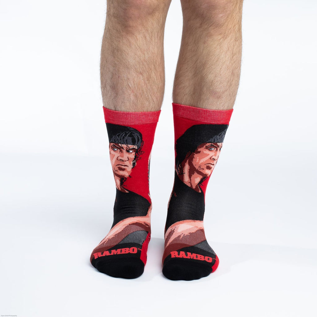 These fun socks feature a cartoon drawing of Sylvester Stallone from the 1982 movie Rambo giving a thumbs up, with the title written in red near the toe. The background of the sock is a bright red while the toe and heel are black. The active fit socks sport elastic arch bands to contour to your feet and provide support.