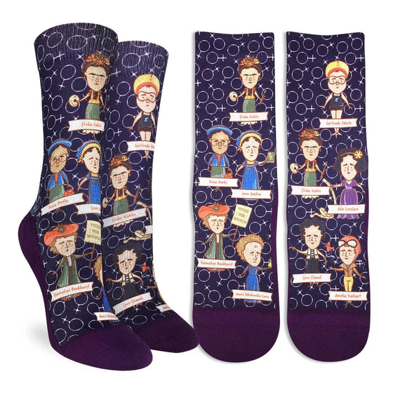 In honor of some of history's great women, these purple socks feature cartoon-like designs of Frida Kahlo, Ada Lovelace, Amelia Earhart, Coco Chanel, Emmeline Pankhurst, Gertrude Ederle, Jane Austen, and Rosa Parks. the socks are purple with the female circle cross symbol adorning the background. 48% Polyester, 45% Cotton, 5% Elastic, 2% Spandex
