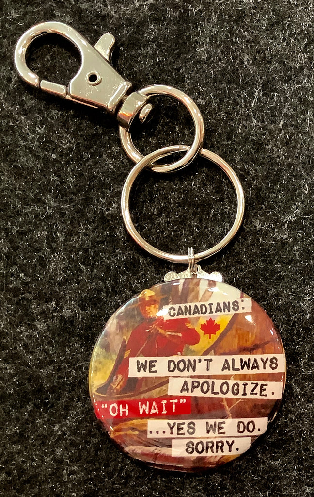 "Round tab featuring a Canadian mountie and the words ""Canadians: we don't always apologize. Oh Wait...Yes we do. Sorry"" attached to a key ring and a clasp"