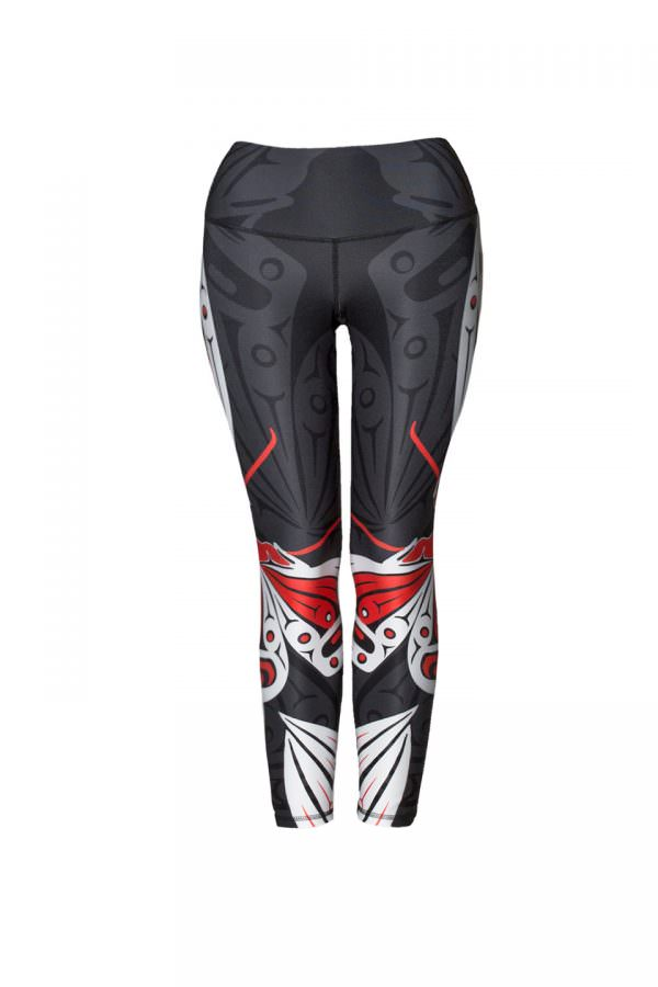 These black, red and white leggings are decorated with two Haida butterflies, one on each leg. The butterflies fly around the outside of the pants toward the front. Part of their wings and antennae can be seen here.