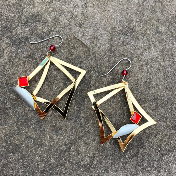 A pair of large hook earrings featuring two bright gold rectangles, a silver accent, and a square of clear red glass