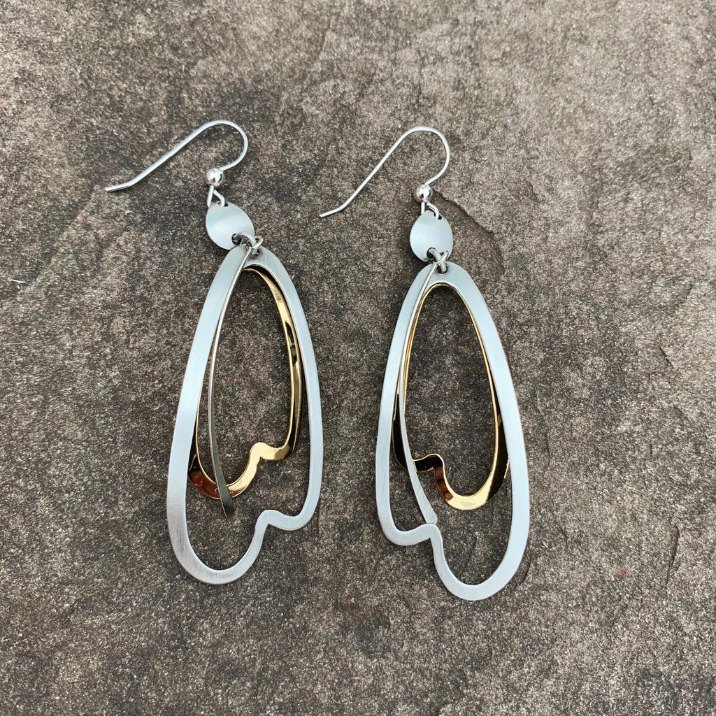 A pair of large hook earrings featuring an abstract shape resembling an elongated, upside-down heart in matte silver. An identical shape in bright gold hangs behind it.