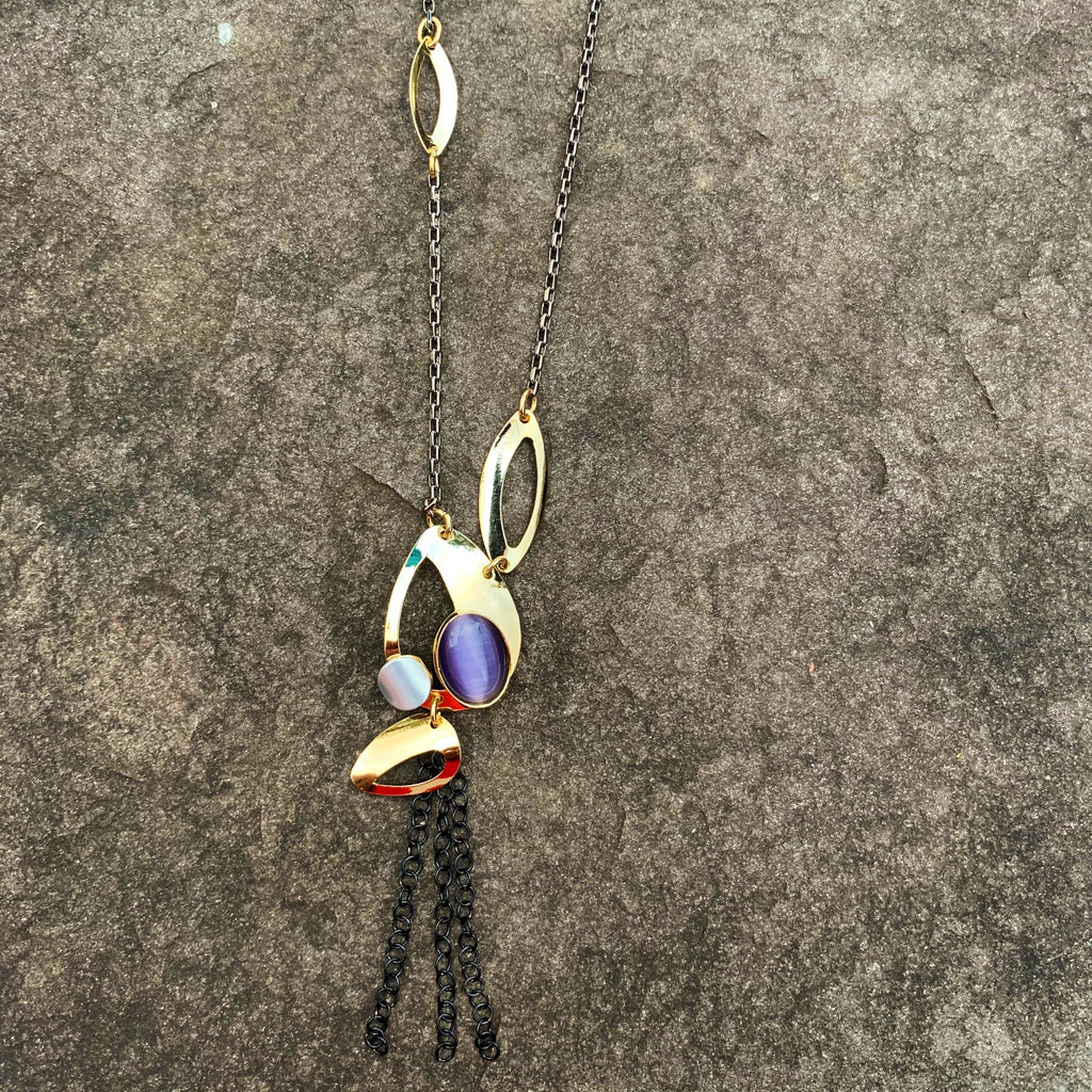 A necklace featuring  several gold leaf shapes and a purple cat's-eye glass gem. Three short brass chains hang from the bottom of the necklace