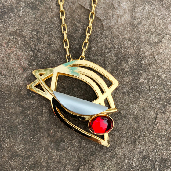A necklace featuring several gold leaf shapes and a bright red glass gem