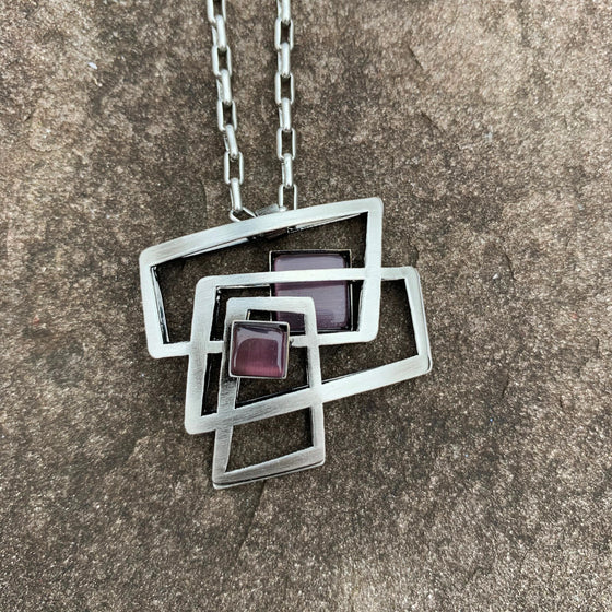A necklace featuring concentric rectangles of purple cat's-eye glass and silver metal