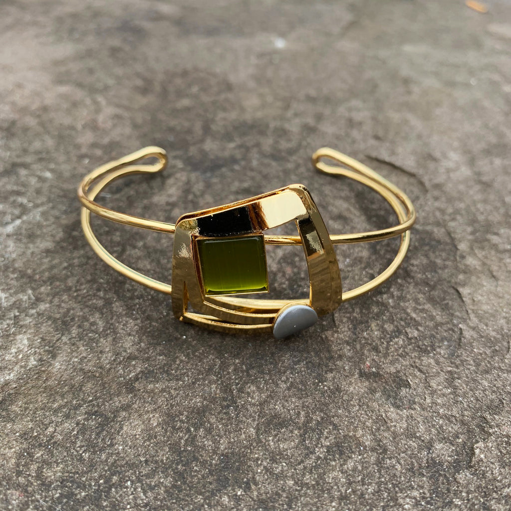 A cuff bracelet featuring a gold, slightly distorted square with a silver accent and containing a square of green cat's-eye glass