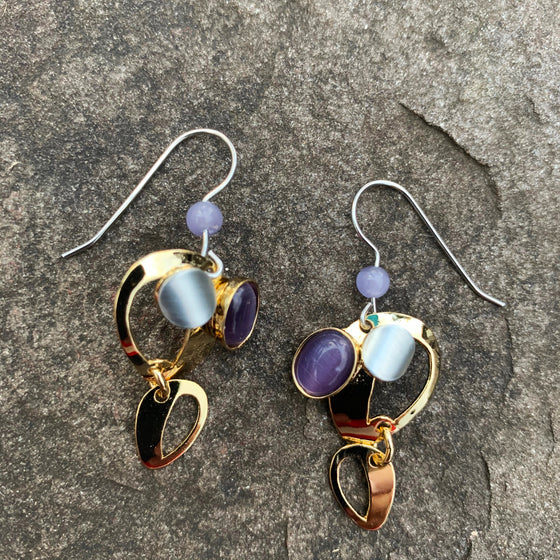 A pair of hook earrings featuring two golden, upside-down teardrops shapes. Where the teardrops meet the earring hook is a small silver accent and a purple cat's-eye glass bead.