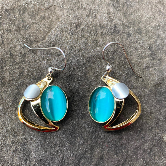 A pair of hook earrings featuring a gold crescent cradling a large blue cat's-eye glass gem