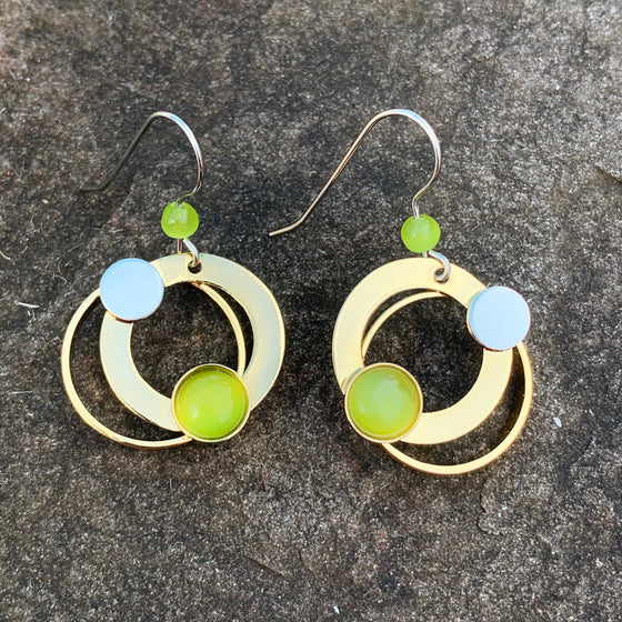 A pair of hook earrings featuring concentric gold rings and a circle of green cat's-eye glass
