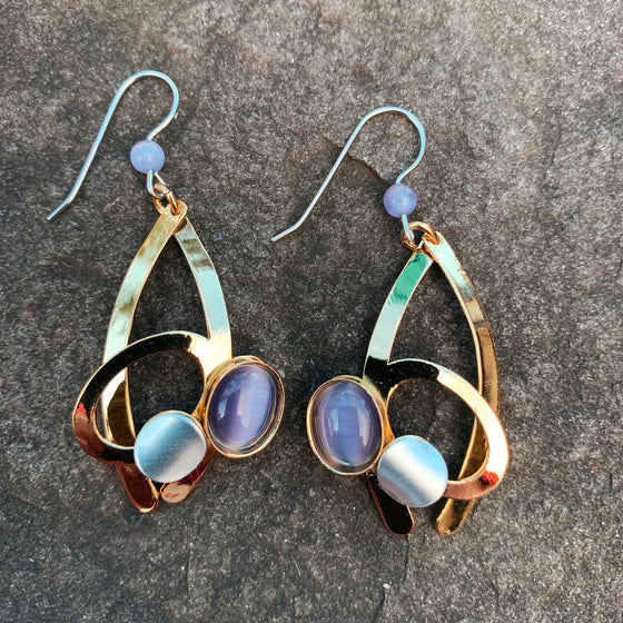 A pair of hook earrings featuring two gold curves. One curve supports a gold ring, a silver accent, and a purple cat's-eye glass bead