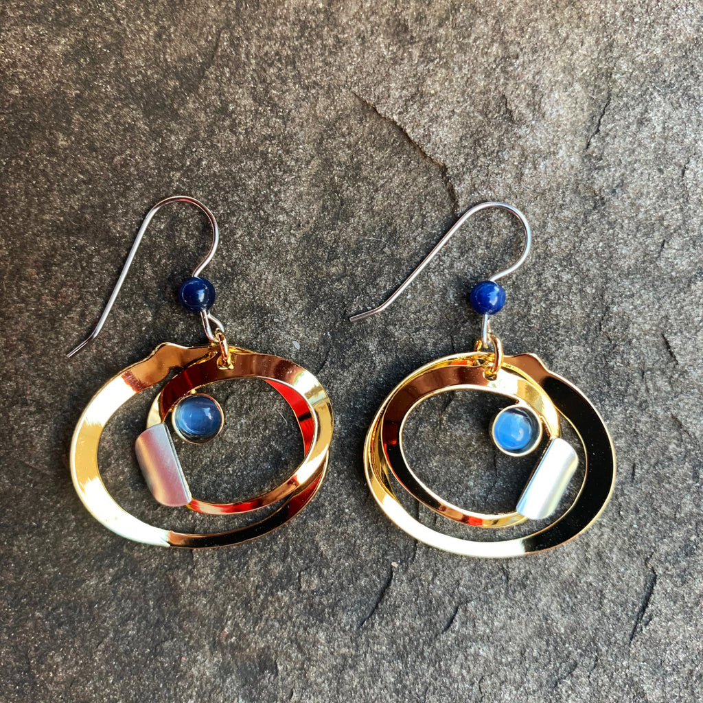 A pair of hook earrings featuring two concentric gold rings. The inner ring has a silver accent and a small blue glass bead