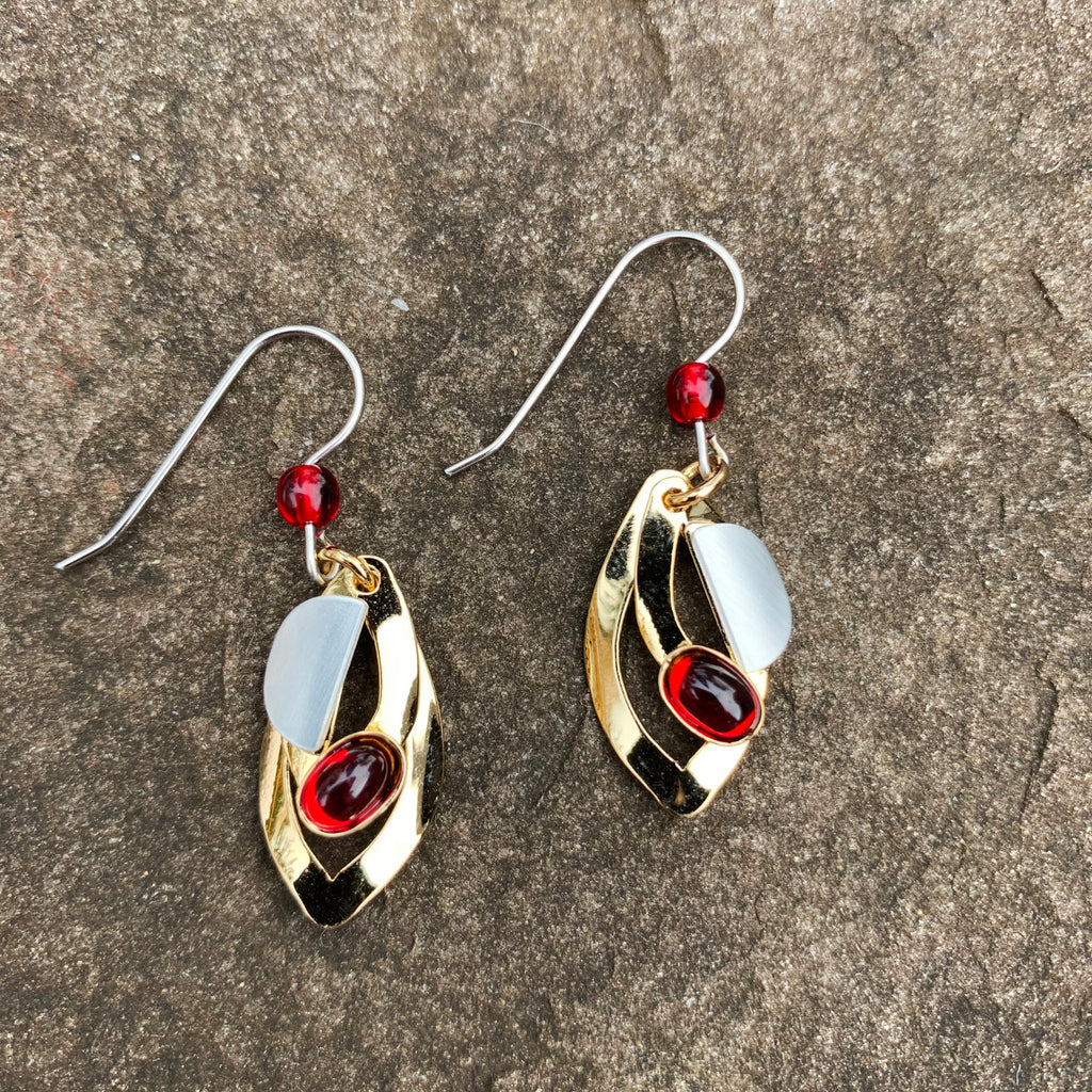 A pair of hook earrings featuring two gold leaf shapes set with a silver semi-circle accent and a red glass gem