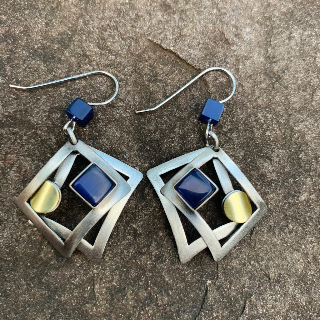 A pair of hook earrings featuring two silver rectangles which frame a gold circle and a square of blue cat's-eye glass