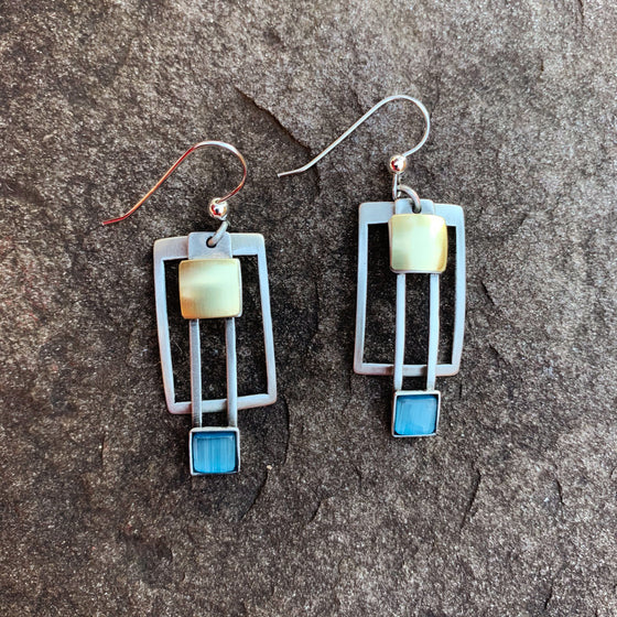 A pair of hook earrings featuring concentric silver rectangles, gold squares, and a square of blue cat's-eye glass
