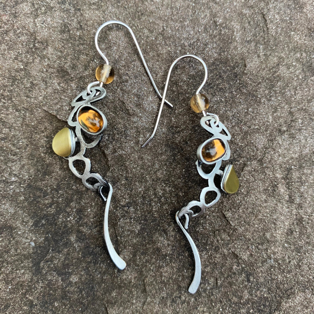 A pair of hook earrings featuring a silver chain like silhouette embellished with a gold accent and an amber glass gem