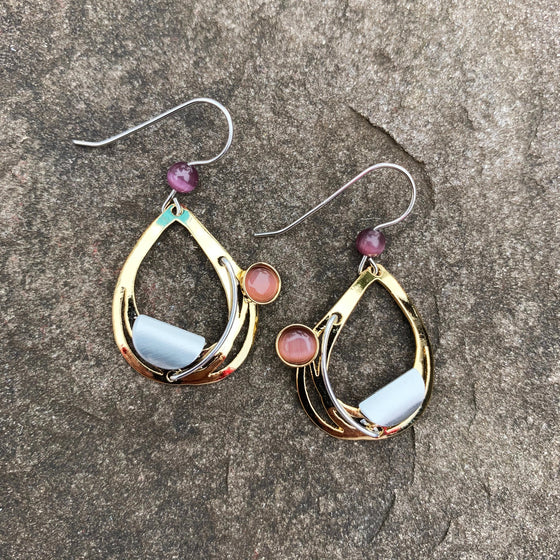 A pair of hook earrings featuring a gold tear drop shape with a silver semi-circle accent and a bead of purple cat's-eye glass