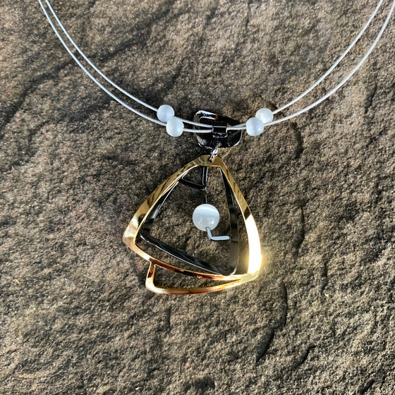 A necklace featuring concentric gold and silver triangles surrounding a white cat's-eye glass bead