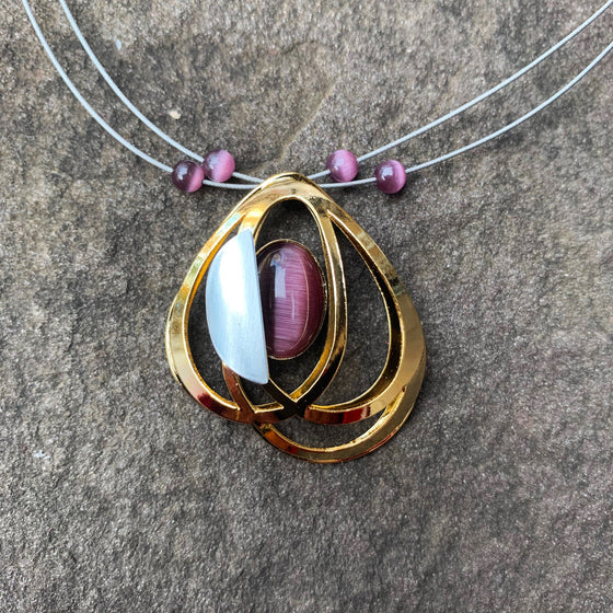A necklace featuring concentric gold loops and a piece of purple cat's-eye glass
