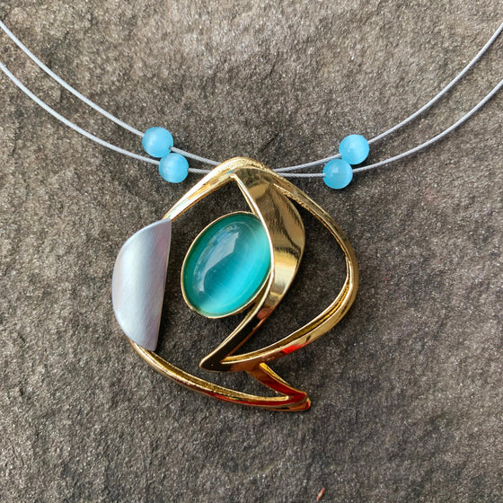 A necklace featuring a turquoise glass cat's-eye gem encircled by an abstract gold shape