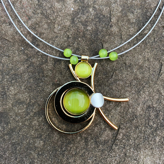 A necklace featuring concentric circles of green cat's-eye glass and gold rings
