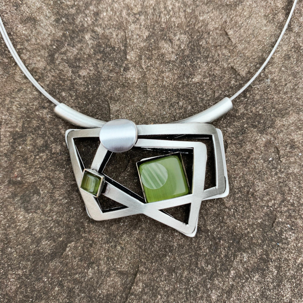 A necklace with concentric silver rectangles and a square piece of green cat's-eye glass