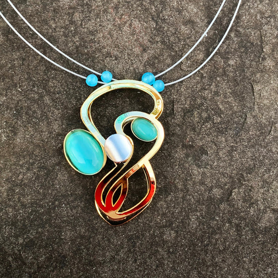 A necklace featuring an abstract figure-eight shape with two turquoise glass cat's-eye gems