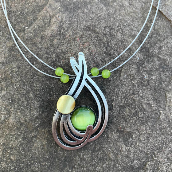 A necklace featuring a green cat's-eye glass gem cradled by several silver swirls