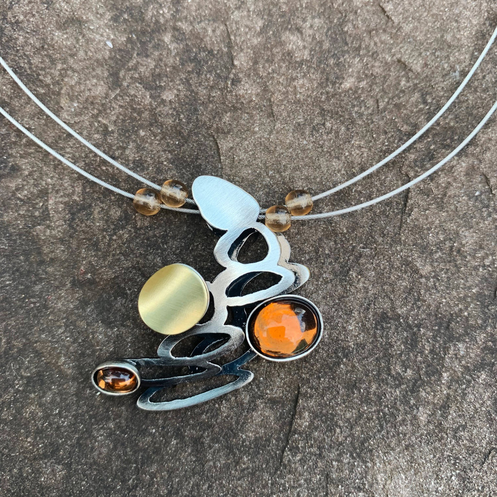 A necklace featuring a cluster of silver loops and two pieces of amber glass