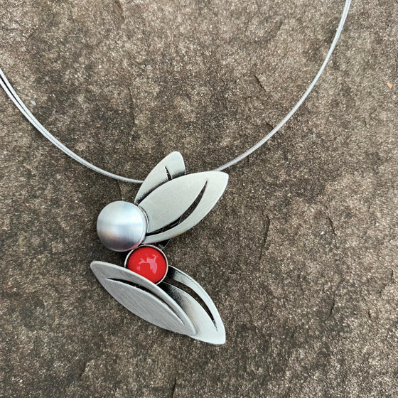 A necklace with four silver leaf shapes and a red glass bead