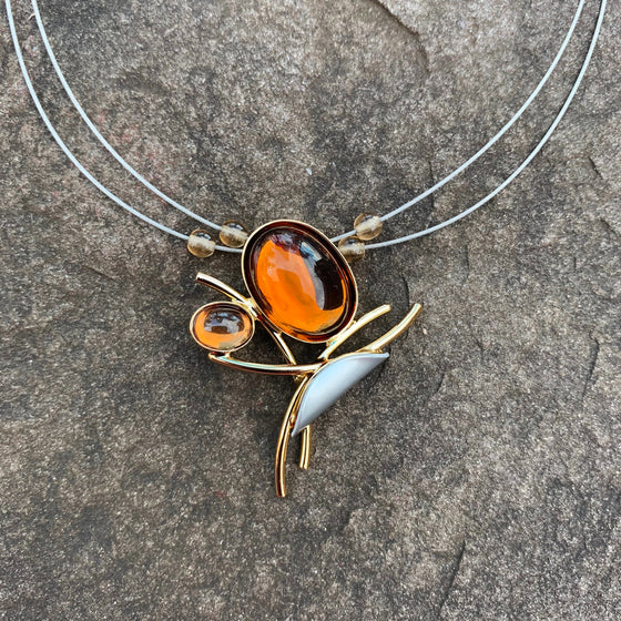 A necklace featuring three overlapping gold wires, a small silver accent, and two amber glass beads