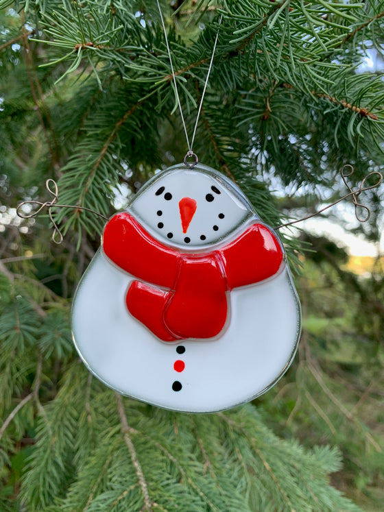 "This fused glass ornament depicts a squat, round snowman with a carrot nose and a ""coal smile"". He wears a thick red scarf. His arms are made of wire and are outstretched as though asking for a hug."