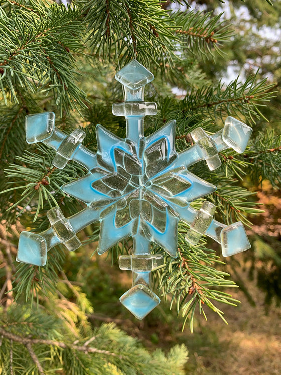 A fused glass ornament depicting a semi-transparent snowflake. The glass is a mix of clear and translucent blue, giving the snowflake a frosty look.