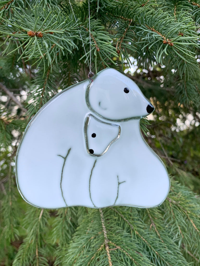 A fused glass ornament showing a mother polar bear and her cub. The cub is tucked snuggly under the mother's chin.